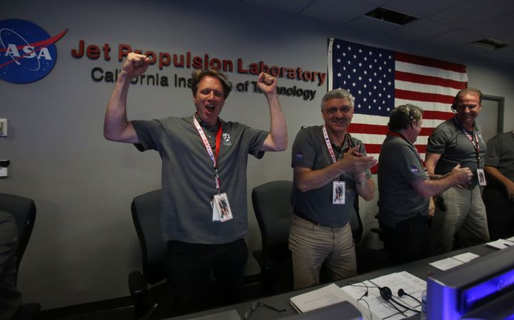 Scott Bolton (L), NASA principal investigator for the Juno mission to Jupiter, reacts as the Juno spacecraft successfully ent