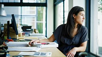 Businesswoman sitting at workstation in office looking out window