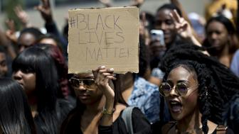 A demonstrator holds a 'Black Lives Matter' sign while chanting towards attendees waiting in line across the street for a rally with Donald Trump, president and chief executive of Trump Organization Inc. and 2016 Republican presidential candidate, at West Chester University in West Chester, Pennsylvania, U.S., on Monday, April 25, 2016. In a move that may be too little too late, Trump's two remaining opponents for the Republican presidential nomination, Ted Cruz and John Kasich, have cut a deal to play in certain states and avoid others in an effort to stop dividing the anti-Trump vote. Photographer: Andrew Harrer/Bloomberg via Getty Images