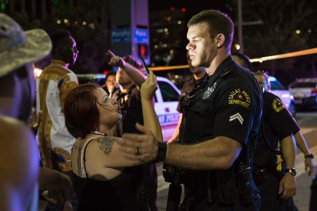 Police attempt to calm the crowd as someone is arrested following the sniper shooting in Dallas