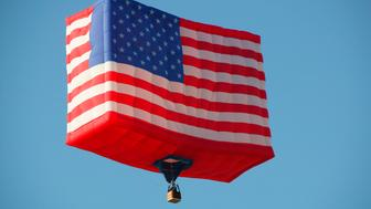 'View of a hot-air balloon shaped like an American flag against blue sky, Balloon Festival, Albuquerque, New Mexico, USA'