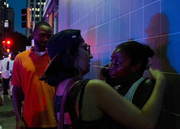 Two witnesses embrace after a Dallas anti-police brutality protest was hit by sniper fire.