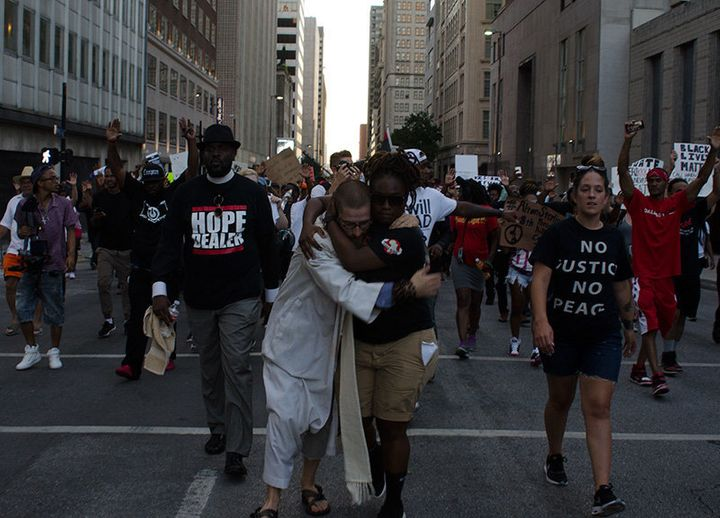 Protesters embrace during a march through downtown Dallas Thursday, July 7.