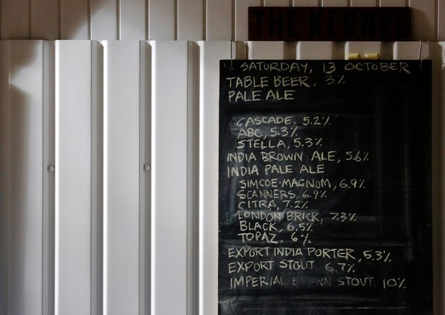 A list of beers and their average alcohol volumes are written on a chalk board at The Kernel micro-brewery...
