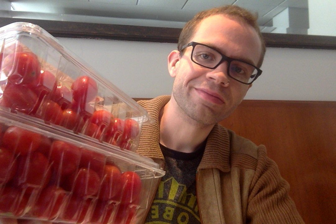 William Reid poses with cherry tomatoes rescued from the trash.