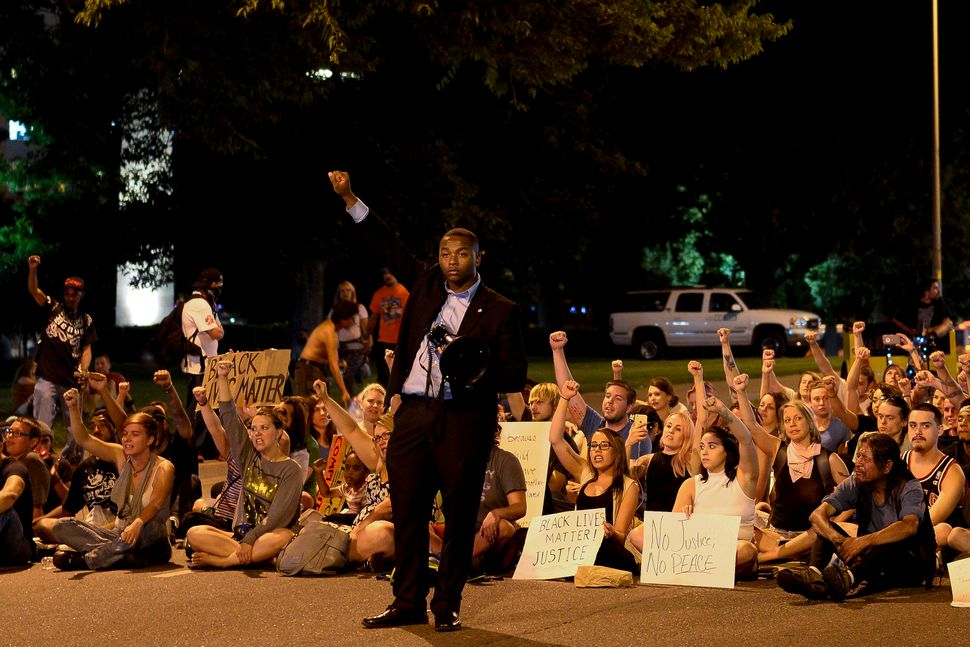 Colorado High School Democrats of America State Chairman Tay Anderson raises his fist with a crowd of protesters as they stan
