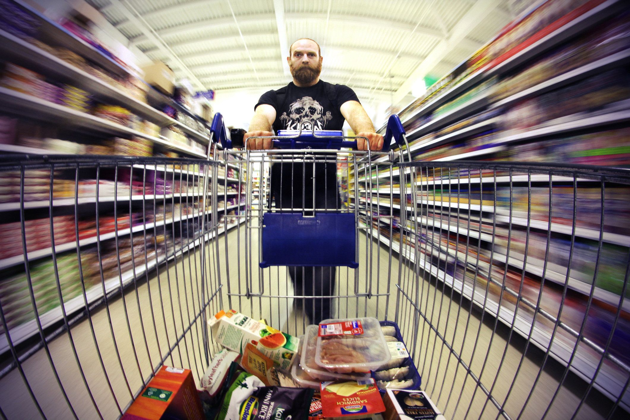 Man pushing shopping trolly full of food with motion blur.