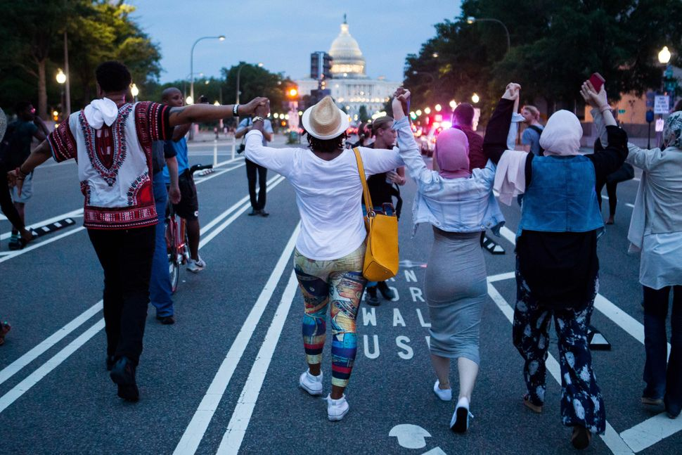 Demonstrators hold hands as they march from The White House to Capitol Hill on July 7, 2016 in Washington, D.C.