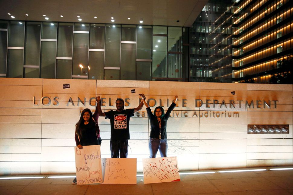 Black Lives Matter activists standtogether after a protest outside the Los Angeles Police Department headquarters.