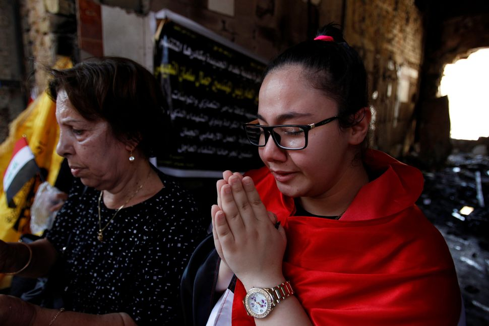 Christian Iraqis pray for the victims of the bombing at the site of the attack on Friday.