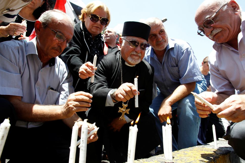 Christians light candles at the site of the attack.