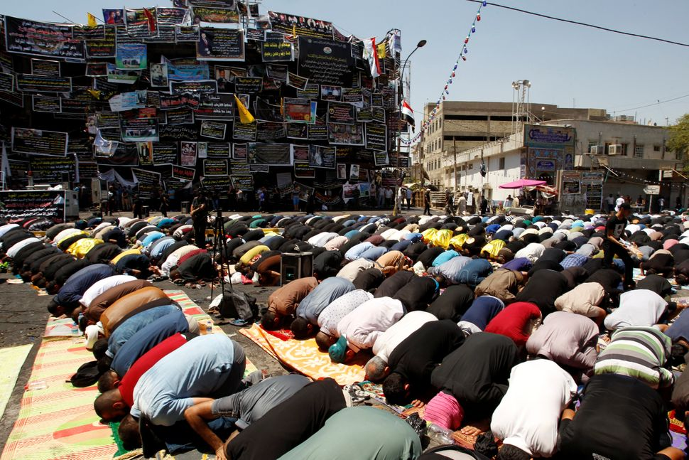 Iraqis attend Friday prayers at the site of a suicide car bomb attack over the weekend in Karrada, Baghdad.