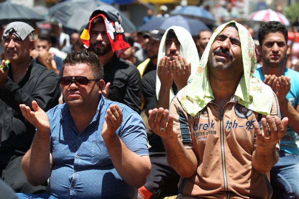 Iraqis pray outside the Karrada shopping center.