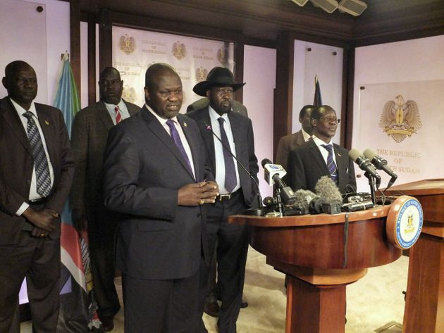 South Sudan First Vice President Riek Machar (L) and President Salva Kiir (C) told reporters...