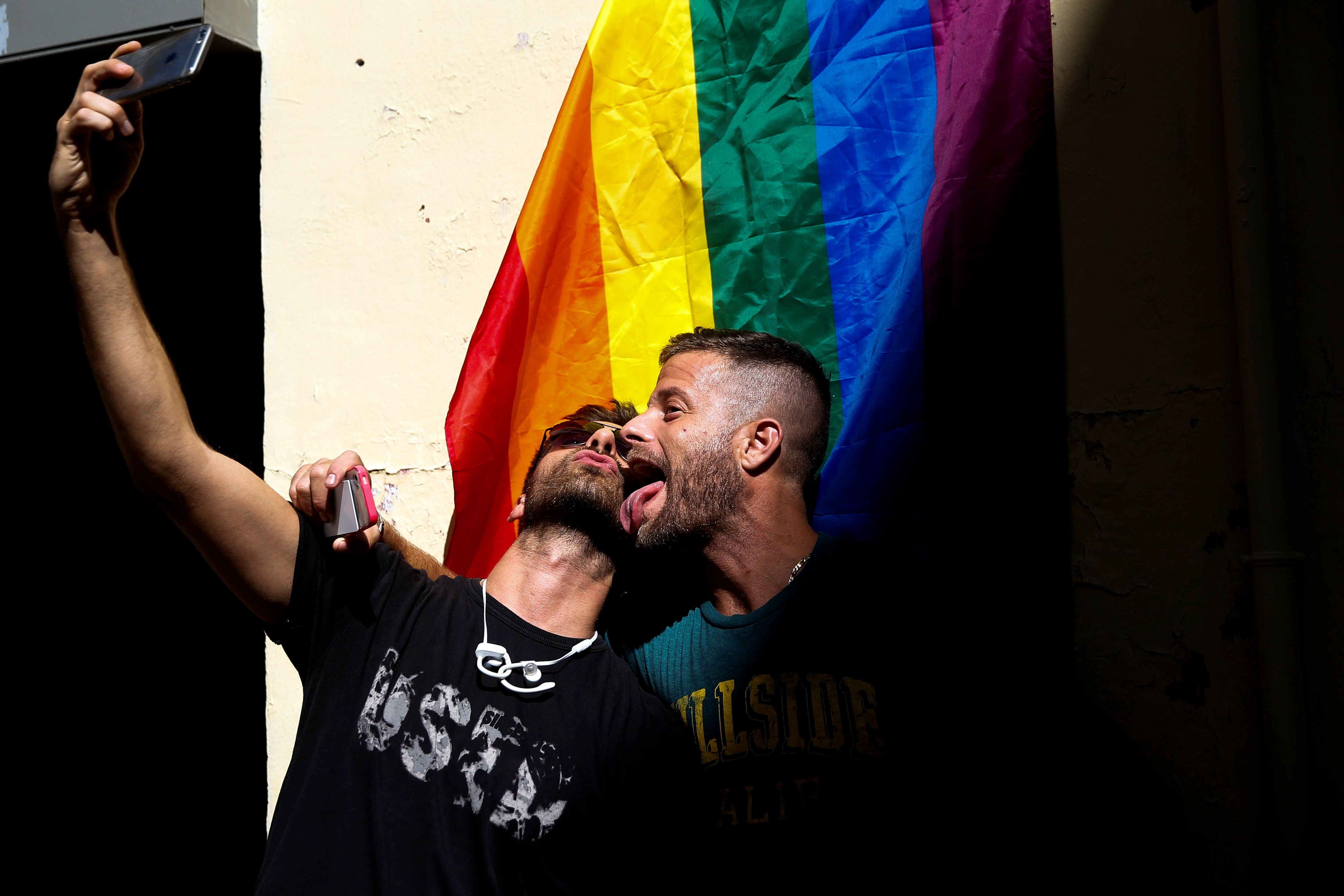 Two men take a selfie by a rainbow flag before the annual race on high heels during Gay Pride celebrations in the quarter of Chueca in Madrid, Spain, June 30, 2016. REUTERS/Susana Vera