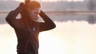 Girl preparing to jogging at morning near a lake