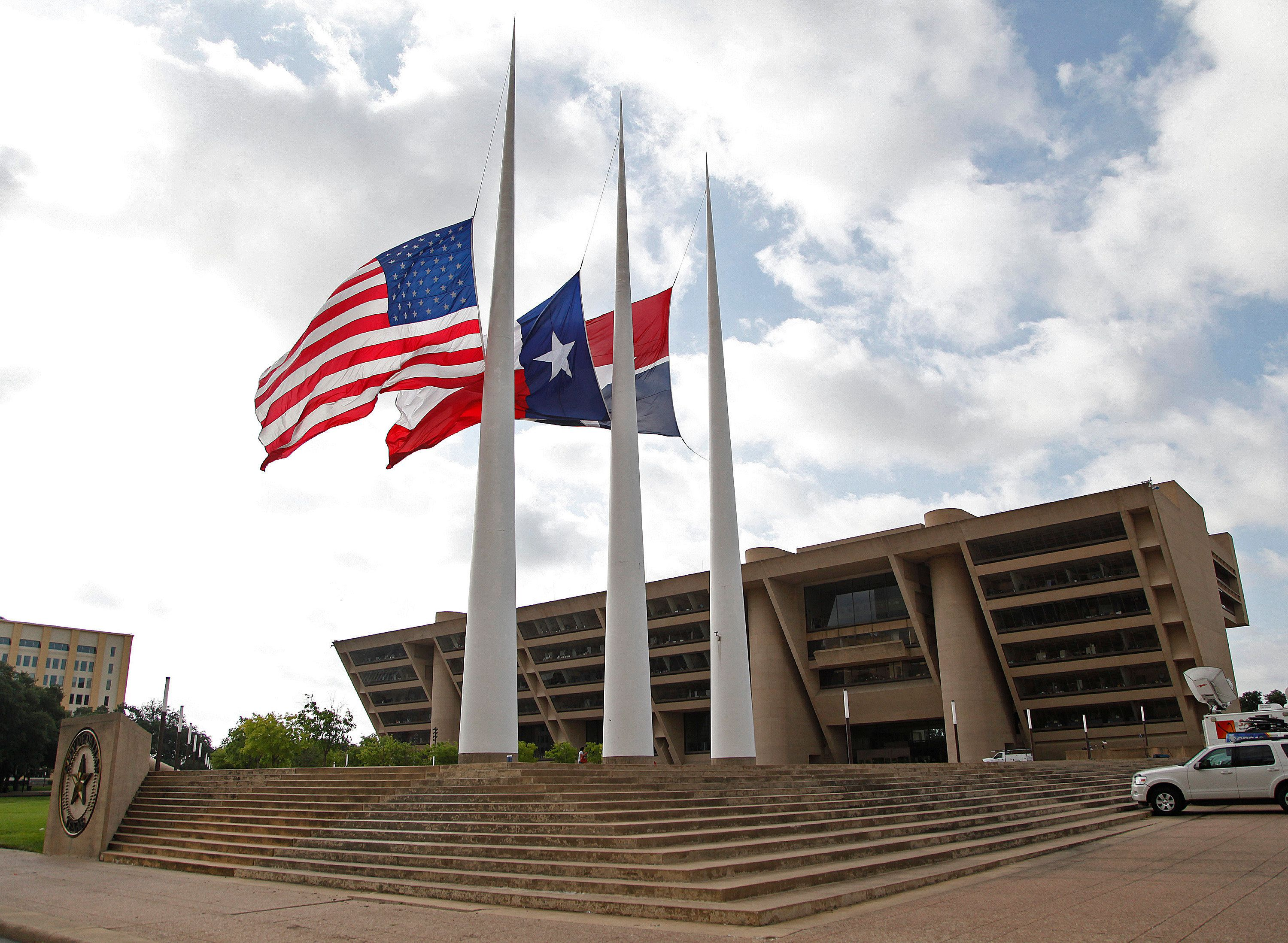DALLAS, TX - JULY 8: Flags fly at half mast at Dallas City Hall following the fatal shootings of five police officers on July 8, 2016 in Dallas, Texas. Micah Xavier Johnson has been identified as the suspected sniper in the fatal shooting of five police officers, and injuring seven more at a Black Lives Matter demonstration held on July 7, 2016 in Dallas, Texas. (Photo by Stewart  F. House/Getty Images)