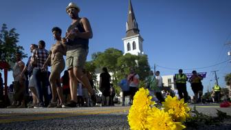 "People walk past a bunch of flowers left in memorial on the ground as they take part in a ""Black Lives Matter"" march past Emanuel African Methodist Episcopal Church in Charleston, June 20, 2015. Dylann Roof, a 21-year-old with a criminal record, is accused of killing nine people at a Bible-study meeting in the historic African-American church in Charleston, South Carolina, in an attack U.S. officials are investigating as a hate crime.      REUTERS/Carlo Allegri"