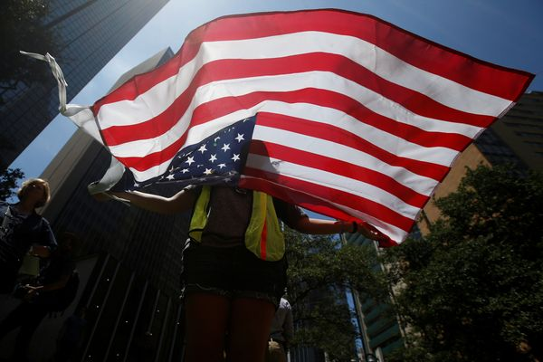 A woman holds a U.S. flag during a prayer vigil in a park following the multiple police shooting in Dallas, Texas, U.S., July