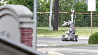 HUTCHINS, TX - JUNE 13: Dallas Police use a robot to gain access to an armoured van, which authorities believed was rigged with explosives, and was driven by a suspect who attacked Dallas Police Headquarters in Dallas, Texas, June 13, 2015. A lone shooter in an armored van, believed to be rigged with explosives, opened fire on the Dallas Police Headquarters early Saturday morning. The shooter reportedly unleashed multiple rounds and planted explosive devices around the station before leading police on a chase that ended in a standoff in the parking lot of a fast food resturant. (Photo by Stewart F. House/Getty Images)