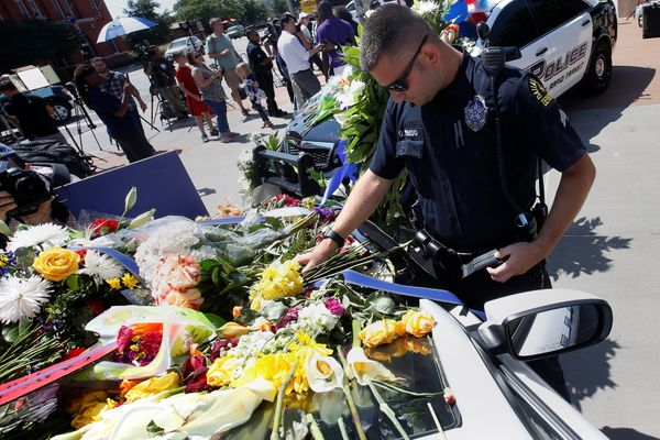 A Dallas police officer observes a moment of silence after putting some flowers on a police car that makes up part of a makes