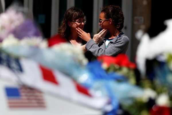 Ginny Alexander (R) and her mother Ariel Alexander react behind a police car that makes up part of a makeshift memorial at Po