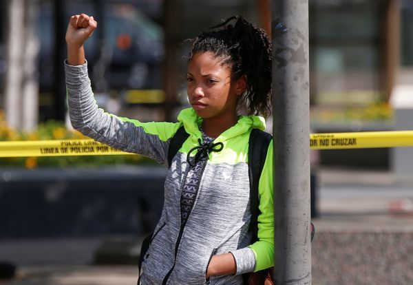 Dajia Dominguez,14, from Dallas, stands with her fist up at Rosa Parks Plaza near the shooting scene in Dallas, Texas, U.S.,