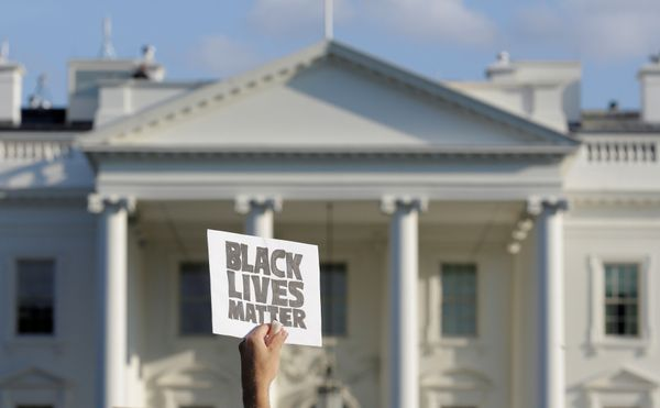 A demonstrator with Black Lives Matter holds up a sign during a protest in front of the White House in Washington, U.S., July