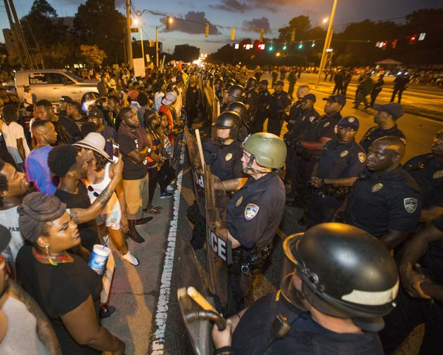 Protesters face off with Baton Rouge police in riot gear across the street from the police department...