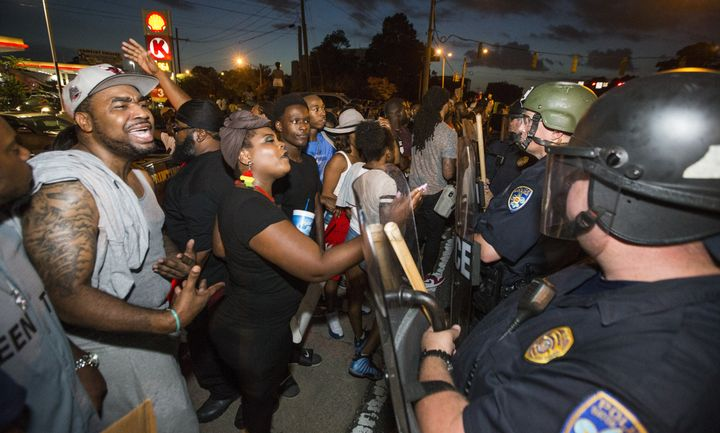 Protesters face off with Baton Rouge police in riot gear across the street from the police department on July 8, 2016 in Bato