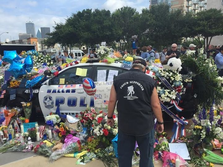 A man stands at an impromptu memorial set up outside the Dallas Police Department on Saturday.