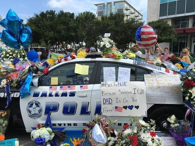 A cop car in Dallas is coveredin flowers and messages of love Saturday, July 9, 2016.
