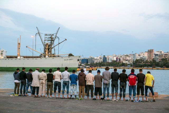 A group of Muslim men line up by the docks of the Athenian port of Piraeus to perform evening prayer.
