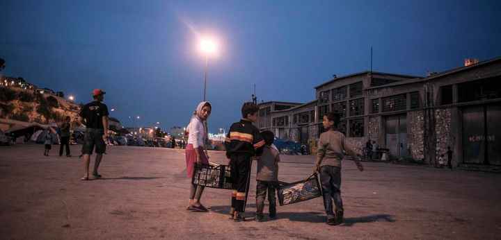 Members of a family walk back from communal taps to their tent in the temporary campsite at the port of Piraeus, close to whe