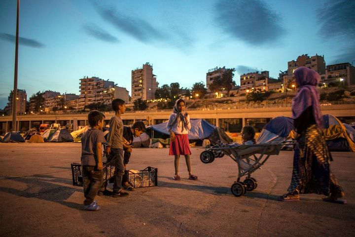 A refugee family stand at dusk against a battery of concrete apartment blocks in the Athenian port of Piraeus.