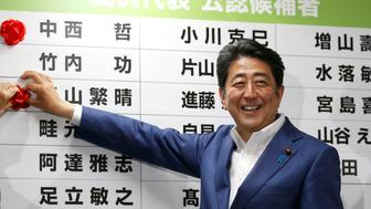 Japan's Prime Minister Shinzo Abe, who is also leader of the ruling Liberal Democratic Party (LDP), smiles as he puts a rosette on the name of a candidate who is expected to win the upper house election, at the LDP headquarters in Tokyo, Japan July 10, 2016.  REUTERS/Toru Hanai