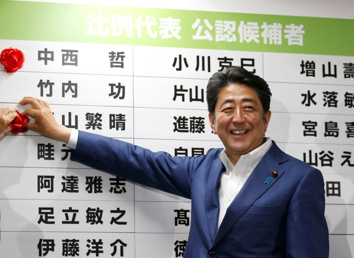 Japan's Prime Minister Shinzo Abe, leader of the ruling Liberal Democratic Party (LDP),  puts a rosette on the name of a