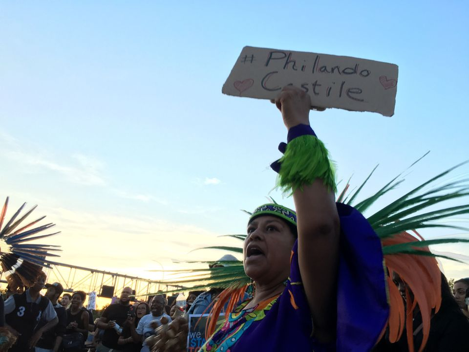 A member of the indigenous Mexican Mexica Tribe from the Kalpulli Yaocenoxtli dance group holds a sign for Philando Castile,
