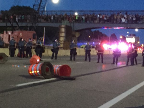 St. Paul police officers stand in a line with shields and batons opposite protesters who took over I-94 on July 9.