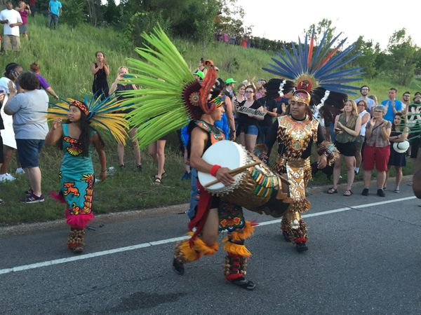 Members of the indigenous Mexican Mexica Tribe from the Kalpulli Yaocenoxtli dance group cross the embankment from the I