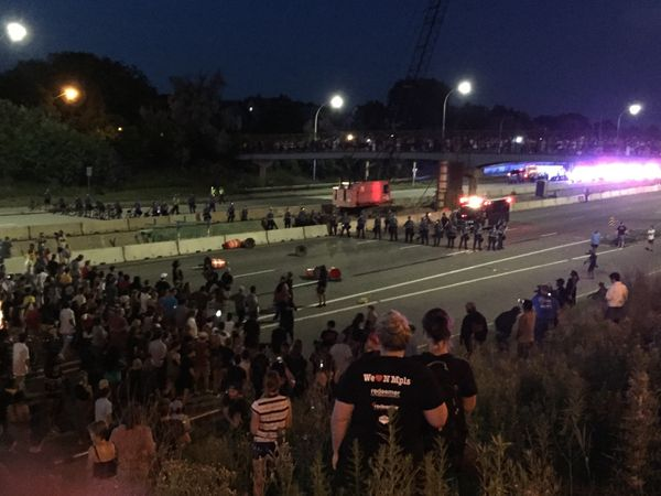 Protesters hold a line in front of St. Paul police who stand ready with shields and batons on I-94 July 9.