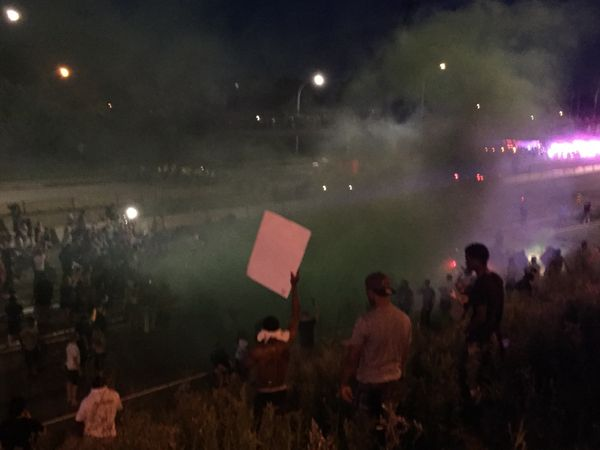 St. Paul police throw an inert smoke grenade to disperse protesters gathered on I-94 on July 9.