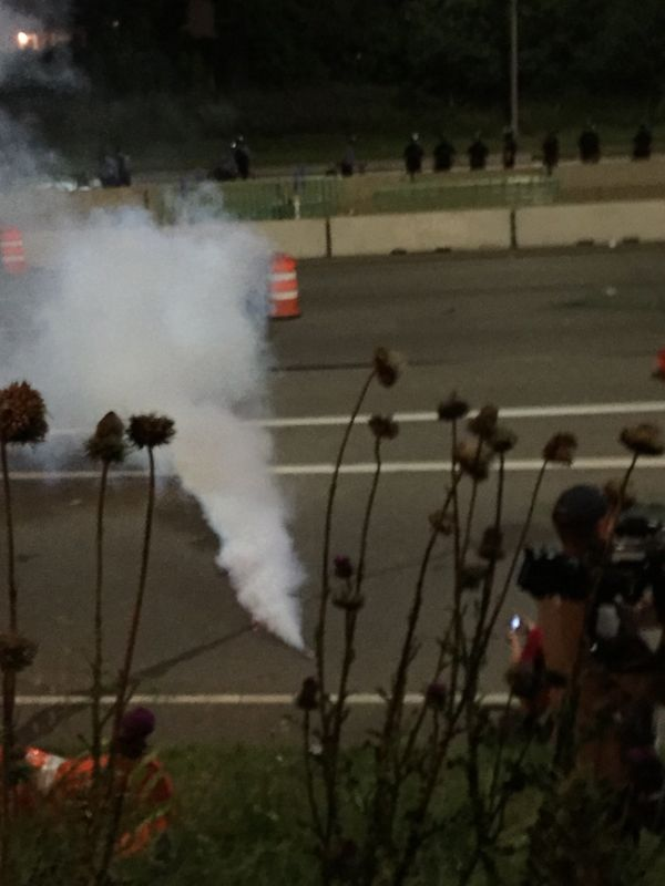 Protesters scatter after a canister lands near a group gathered on I-94 in St. Paul on July 9.