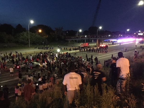 Onlookers and some protesters watch from the embankment above I-94 as the protest line and St. Paul police stand off on July