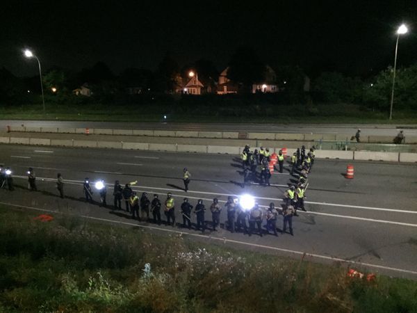 St. Paul police and Minnesota StatePatrol use strobe lights as they prepare to fire rubber bullets, marker rounds and g