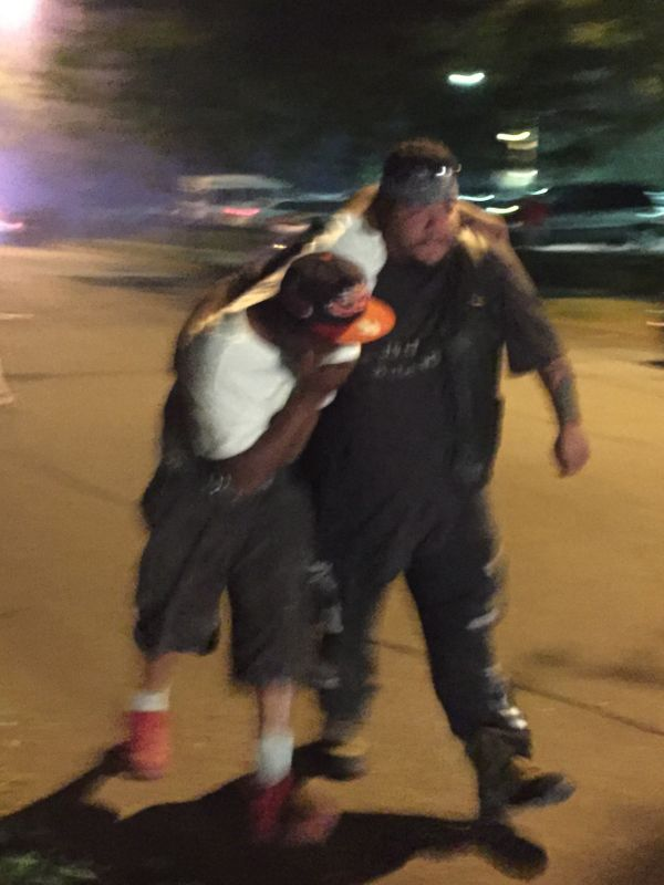 A protester carries a man away after he's hit by what police say was pepper sprayduring the I-94 shutdown protest on Ju