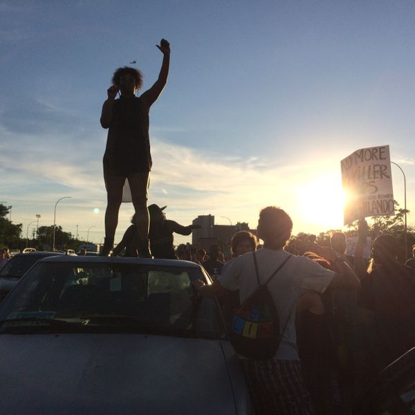 A woman leading the protest march along I-94 addresses the crowd from the back of a pickup truck that managed to enter the fr