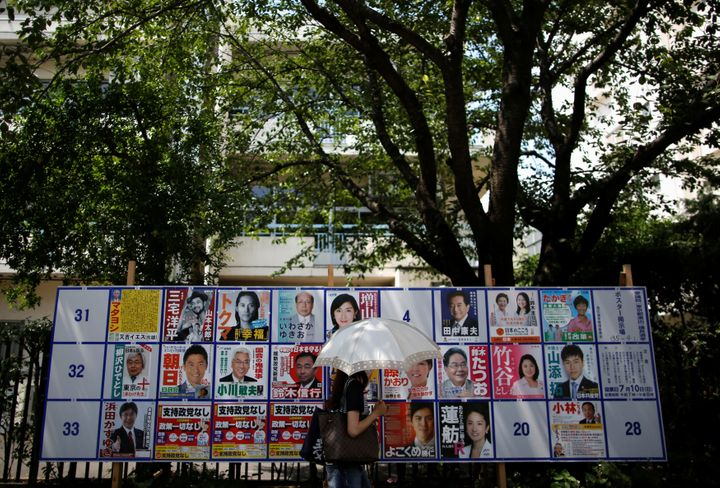A voter walks past in front of election campaign posters for Japan's upper house election, on a street in front of a polling