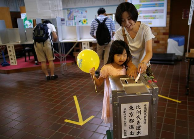 A girl looks on as her mother casts her ballot for Japan's upper house election at a polling station...