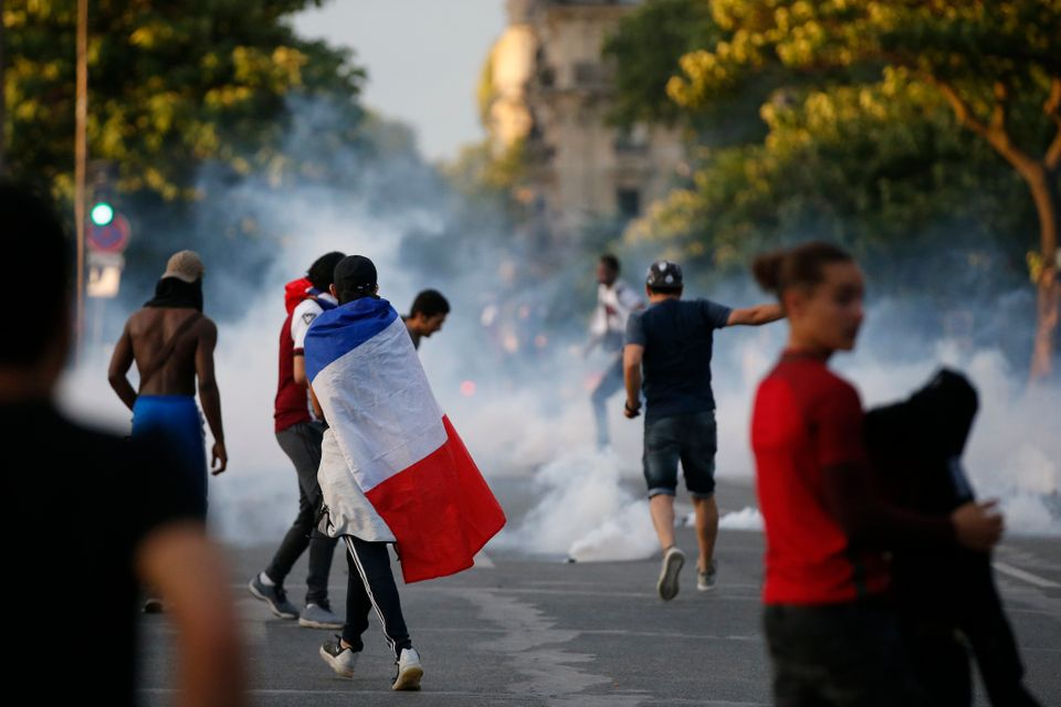 Tear gas floats in the air during clashes near the Paris fans zone during the Portugal v France EURO...